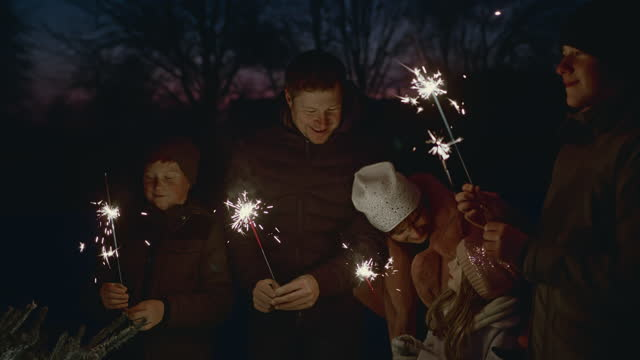slo mo family holding sparklers while standing beside a christmas tree on the backyard - family with three children stock videos & royalty-free footage