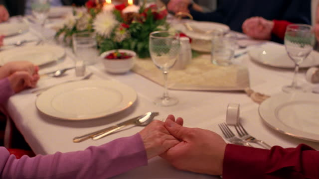 A family holds hands around a dinning table while saying grace at a formal Christmas dinner.