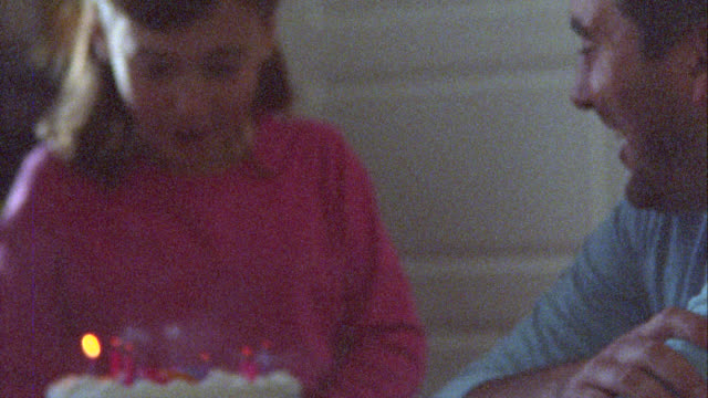 family home video of daughter blowing out candles on birthday cake on film. - candeline di compleanno video stock e b–roll