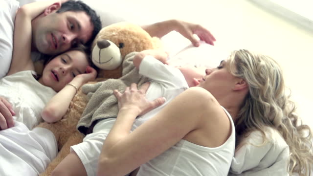 slow motion - family hug bed fun sunday morning - bed stock videos & royalty-free footage