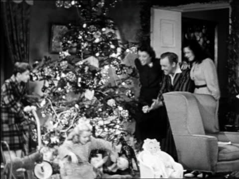B/W 1950 family hugging by tree on Xmas morning / educational
