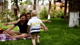 Family idyll. Happy child running to his parents in a blurred perspective. Close up of young couple hugging his little blonde son while sitting on the grass, plaid. Picnic in the park. Slow motion