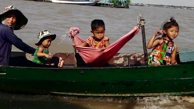 stockvideo's en b-roll-footage met a family in a boat travels on a river in cambodia - familie met drie kinderen
