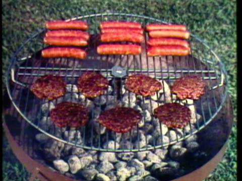 1953 montage family in back yard, man cooking on grill / cu hamburgers and hot dogs on charcoal grill / pan food sitting on picnic table / ws man at barbeque grill and woman placing food on table / usa / audio - hot dog stock videos & royalty-free footage