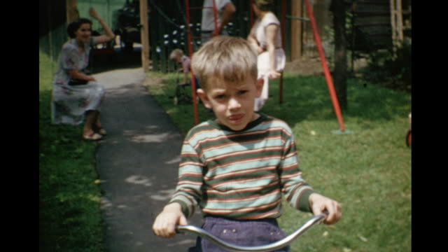 vídeos y material grabado en eventos de stock de 1952 home movie family in backyard with kids riding tricycles / toronto, canada - 1952