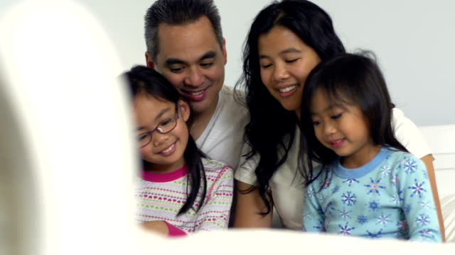 family in bed together reading - filipino ethnicity stock videos & royalty-free footage