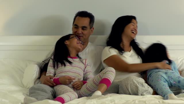 vídeos y material grabado en eventos de stock de familia en la cama juntos - pijama