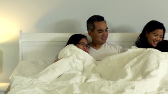 family in bed together - fatcamera stock videos & royalty-free footage