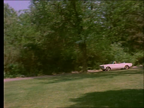 1963 family in convertible pulls into drive with woman on lounge chair (corvair) / corvette parked - family convertible stock videos & royalty-free footage