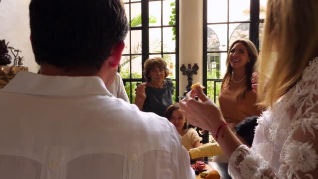 vídeos y material grabado en eventos de stock de ms family in discussion while eating appetizers before celebration meal - plato de comida