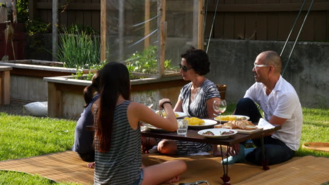 MS TD Family in discussion while eating dinner in backyard of home on summer evening