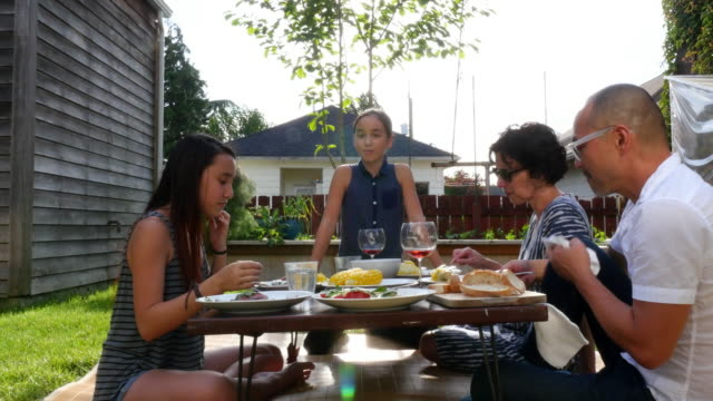 MS Family in discussion while eating dinner in backyard on summer evening