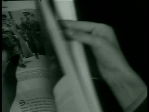 family in home w/ young adult males holding newspapers. female hands turning page of magazine w/ articles & photographs of german nazi soldiers,... - rivista pubblicazione video stock e b–roll