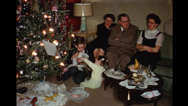 vídeos de stock, filmes e b-roll de 1957 home movie family in living room enjoying christmas with boys opening presents and boy sleeping on couch / toronto, canada - 1957