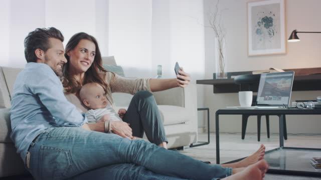 vídeos de stock, filmes e b-roll de família na sala de estar - tirar foto