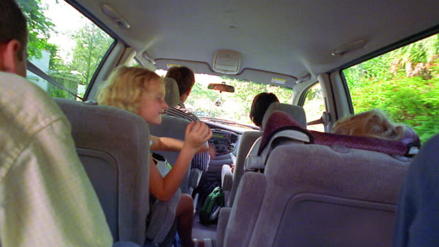 rear view family in minivan with man driving + children playing with soccer balls / florida - drive ball sports stock videos and b-roll footage