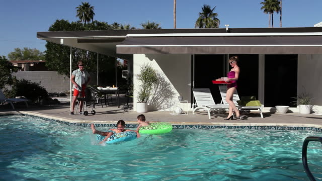 family in outdoor swimming pool - palm springs california stock videos & royalty-free footage
