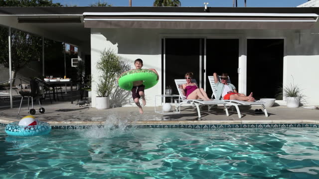 family in outdoor swimming pool - palm springs california pool stock videos & royalty-free footage