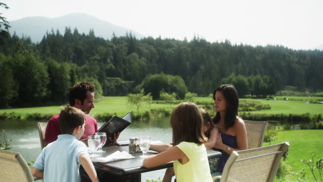 MS DS Family in outdoors restaurant, looking at menu / Squamish, British Columbia, Canada
