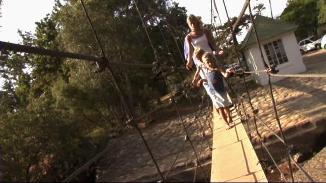 family in park, crossing bridge - gemeinsam gehen stock-videos und b-roll-filmmaterial