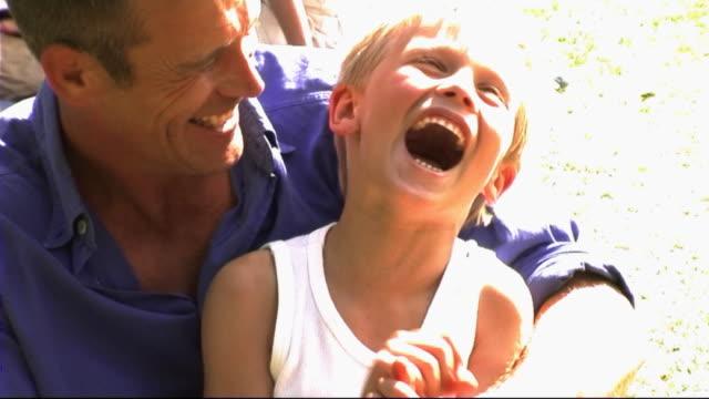 vidéos et rushes de family in park, father and son playing - prendre sur les genoux