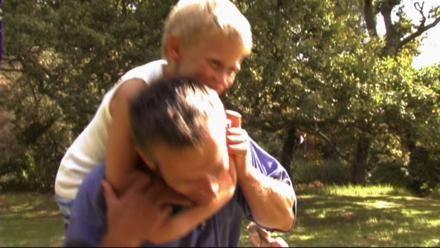 family in park, father and son swinging around - おんぶ点の映像素材/bロール