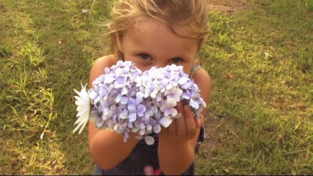 vídeos y material grabado en eventos de stock de family in park, girl with flower - hortensia