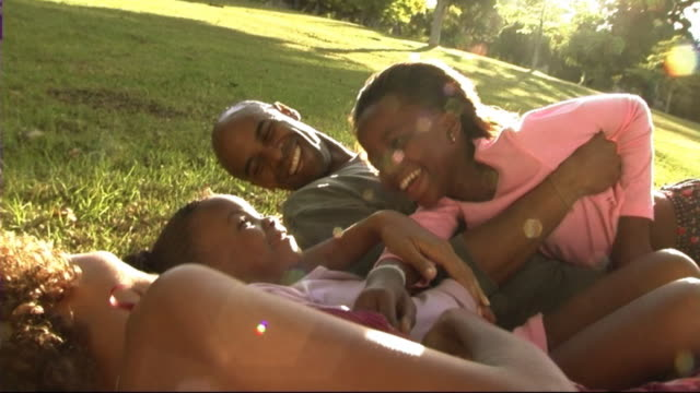 family in park hugging - auf dem rücken liegen stock-videos und b-roll-filmmaterial
