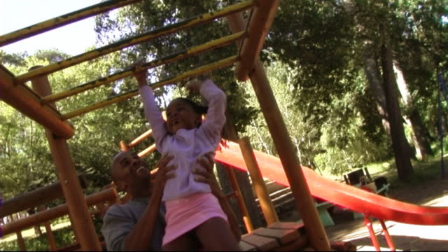 family in park on climbing frame - climbing frame stock videos & royalty-free footage