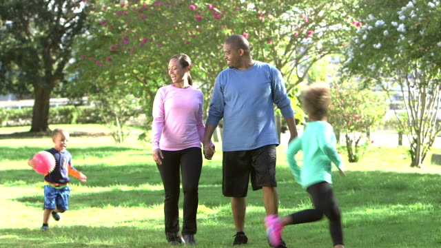 Family in park, parents holding hands, children running