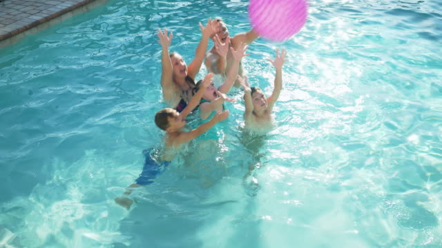 family in pool catching ball, girl with down syndrome - 10 11 years stock videos & royalty-free footage