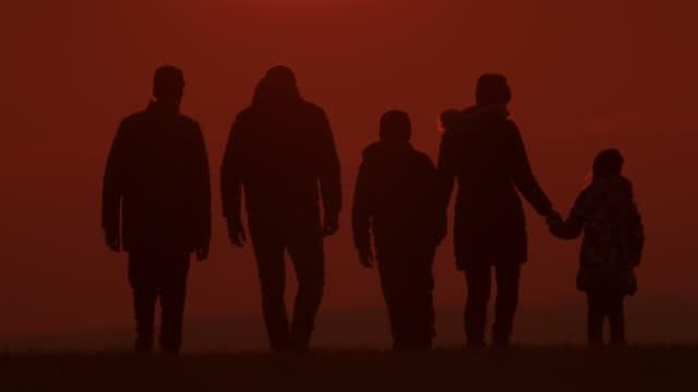 vídeos de stock, filmes e b-roll de slo mo ls família em silhueta desfruta de um passeio em uma colina ao pôr do sol - pessoa irreconhecível