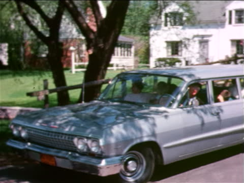 1963 pan family in station wagon turning from driveway onto tree-lined suburban street / ny - suburban stock videos & royalty-free footage