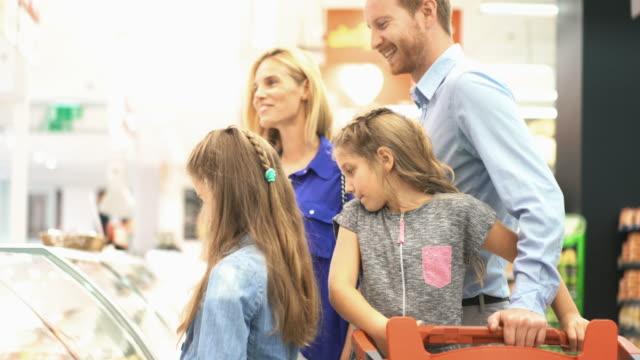 familie im supermarkt - einkaufstasche stock-videos und b-roll-filmmaterial