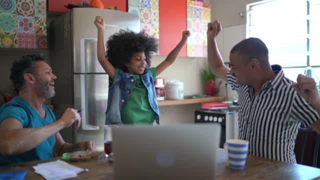 vídeos y material grabado en eventos de stock de familia en la cocina usando computadora portátil y bailando - entusiasmo