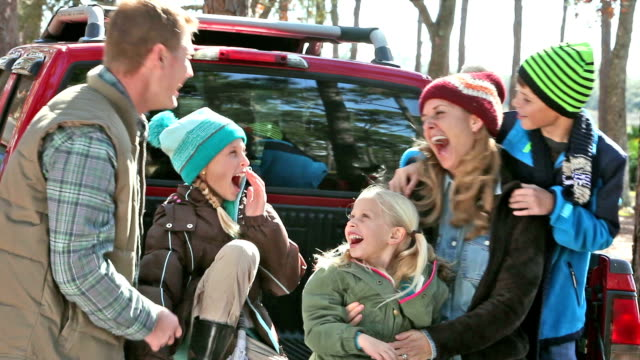 Family in warm clothing laughing on back of pickup