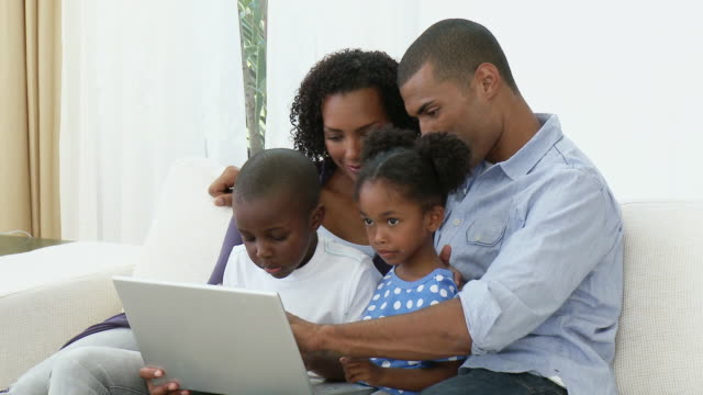MS Family including boy and girl (4-9) using laptop on sofa / Cape Town, South Africa