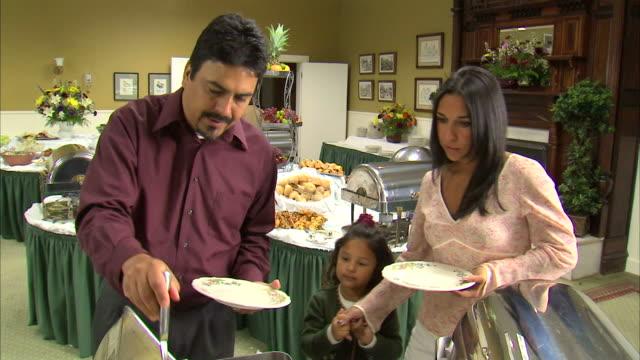 ms family including girl (6-7) putting food on plates at buffet table / heber city, utah, usa - 一人前の量点の映像素材/bロール