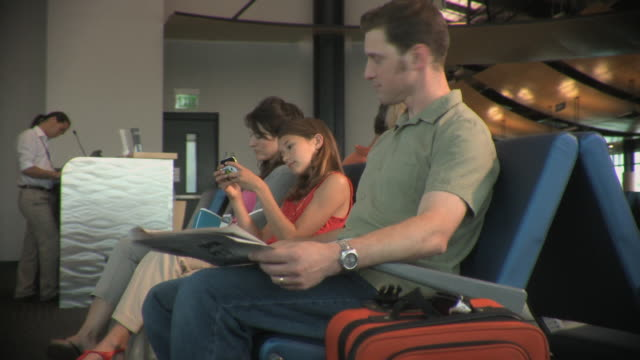 ms ds family including girl (8-9) waiting in airport lounge, appleton, wisconsin, usa - ウィスコンシン州アップルトン点の映像素材/bロール