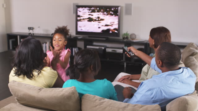 MS Family including girl (4-5) watching TV together, Phoenix, Arizona, USA