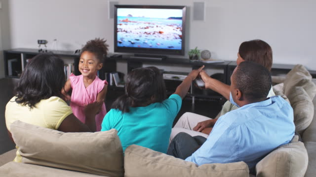 ms family including girl (4-5) watching tv together, phoenix, arizona, usa - watch stock videos & royalty-free footage