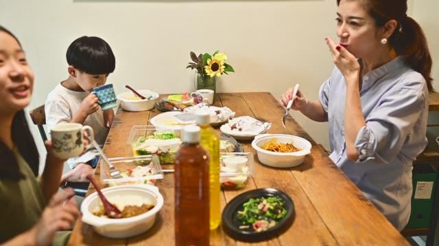 家族は食卓で昼食を食べている。 - カレー料理点の映像素材/bロール