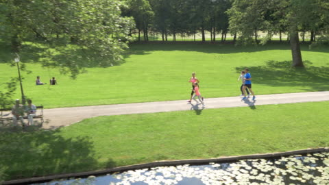 aerial family jogging in the park along a lake - public park stock videos & royalty-free footage