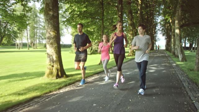 slo mo-ts familie jogging durch den park an einem sonnigen tag - 14 15 jahre stock-videos und b-roll-filmmaterial
