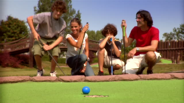 Family kneeling to look at golf ball near edge of hole on mini golf course / boy walking onto green and getting onto stomach to blow ball into hole