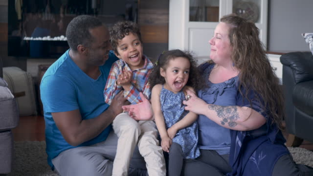 a family laugh together on the couch - cosy stock videos & royalty-free footage