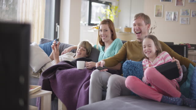 family laughing watching tv on the sofa - portable information device stock videos & royalty-free footage
