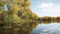 A Family (a Forty-Something Man, a Forty-Something Woman, and a Four Year-Old Boy) Leisurely Stand-Up Paddleboards (SUP) in a Lake in Autumn Under a Sunny Sky in Western Colorado