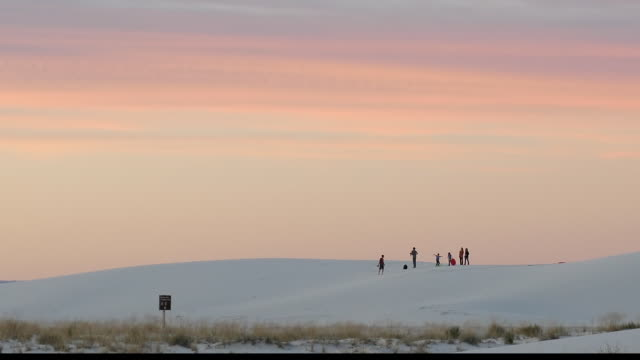 Family life in sand dune at Sunset