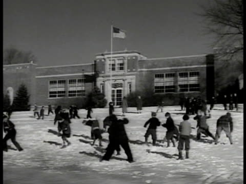family listening to radio ext ws children playing in snow school building w/ american flag bg ms children throwing snow ws church w/ eagle monument... - anno 1941 video stock e b–roll